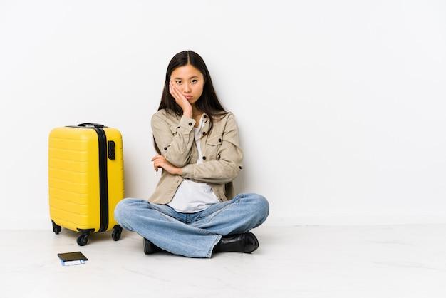 De jonge chinese zitting die van de reizigersvrouw verveeld, vermoeid instapkaarten houden en een ontspannen dag nodig hebben. Premium Foto