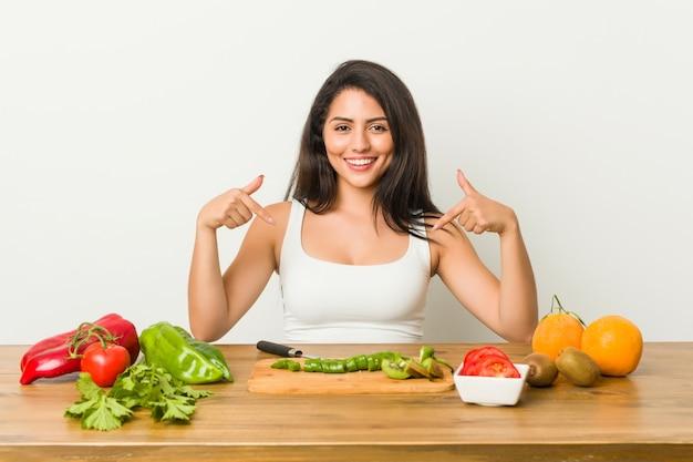 De jonge curvy vrouw die een gezonde maaltijd voorbereidt wijst neer met vingers, positief gevoel. Premium Foto