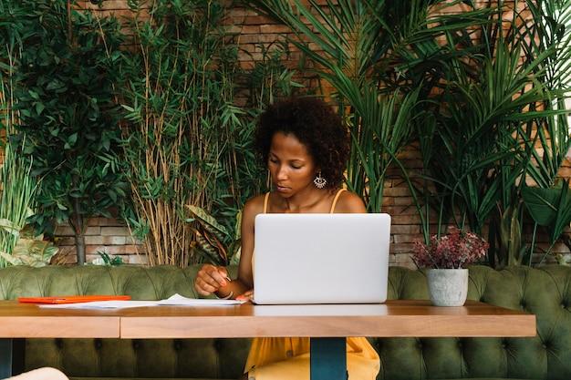 De jonge documenten van de vrouwenlezing met laptop op lijst in het restaurant Gratis Foto