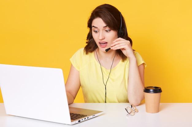 De jonge donkerbruine vrouw met hoofdtelefoon en microfoon, die als exploitant met draagbare computer werken, die geel t-shirt dragen, heeft verbaasde gelaatsuitdrukking, geïsoleerd. Premium Foto