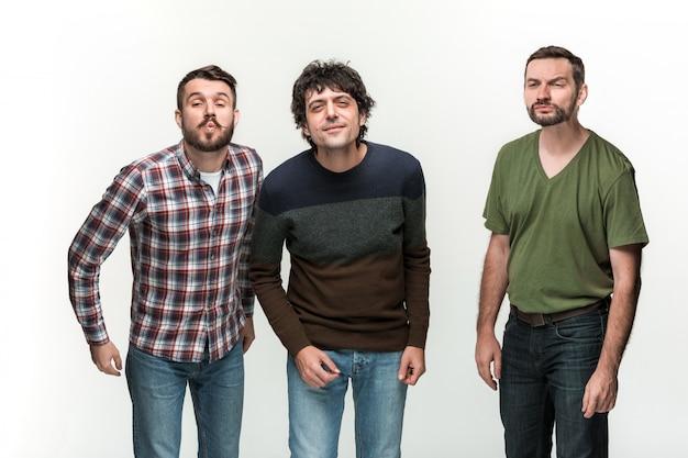 De jonge drie mannen glimlachen, staande op wit met verschillende emoties Gratis Foto