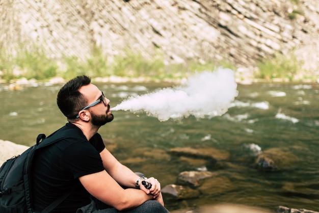 De jonge elektronische sigaret van de reizigersrook dichtbij bergrivier Premium Foto