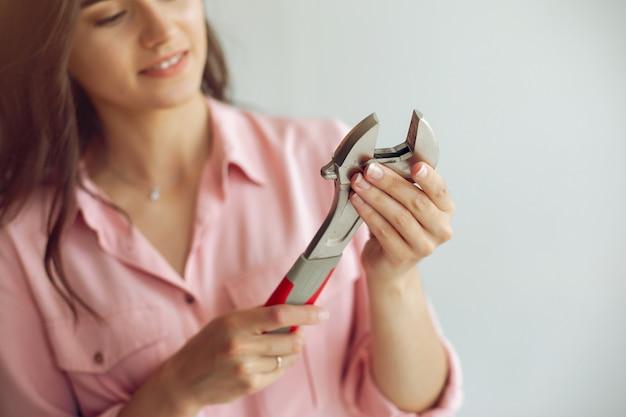 De jonge en leuke vrouw repareert de kamer Gratis Foto