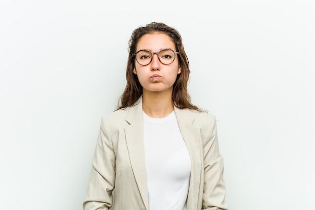 De jonge europese bedrijfsvrouw blaast wangen, heeft uitdrukking vermoeid. gezichtsuitdrukking . Premium Foto