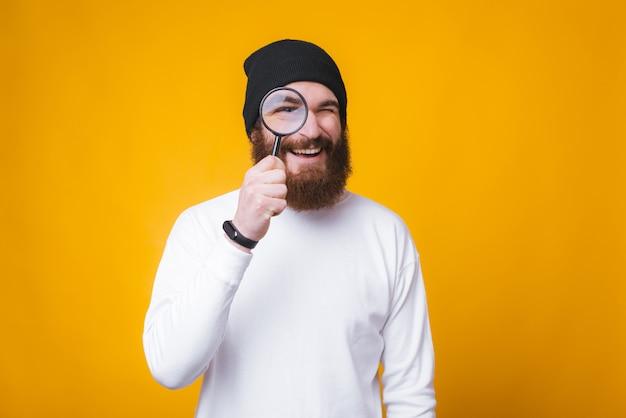 De jonge gebaarde mens kijkt door een vergrootglas en glimlacht dichtbij gele muur. Premium Foto