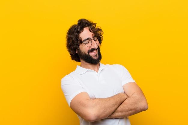 De jonge gekke mens die gelukkig met gekruiste wapens lachen, met een ontspannen, positieve en tevreden stelt gele muur Premium Foto