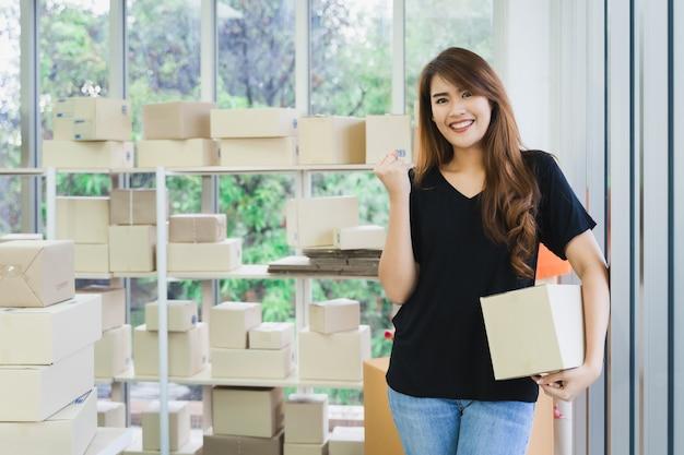 De jonge gelukkige aziatische bedrijfsvrouw is draagt een pakketdoos die en bedrijfssucces verpakken tonen Premium Foto