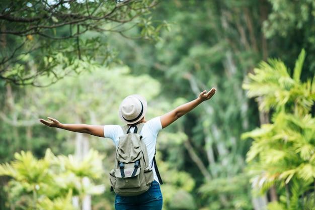 De jonge gelukkige vrouw die met rugzak hand opheffen geniet van met aard. Gratis Foto