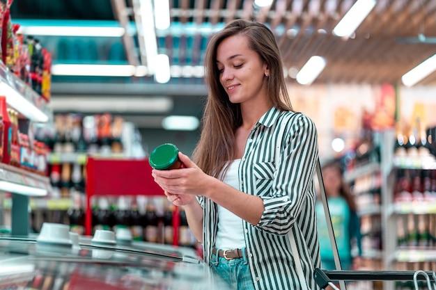 De jonge gelukkige vrouw met boodschappenwagentje kiest, controlerend productenetiket en het kopen van voedsel bij de kruidenierswinkel Premium Foto