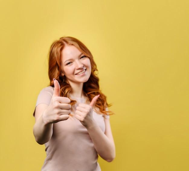 De jonge gelukkige vrouw met rood haar toont duim in goedkeuring Premium Foto