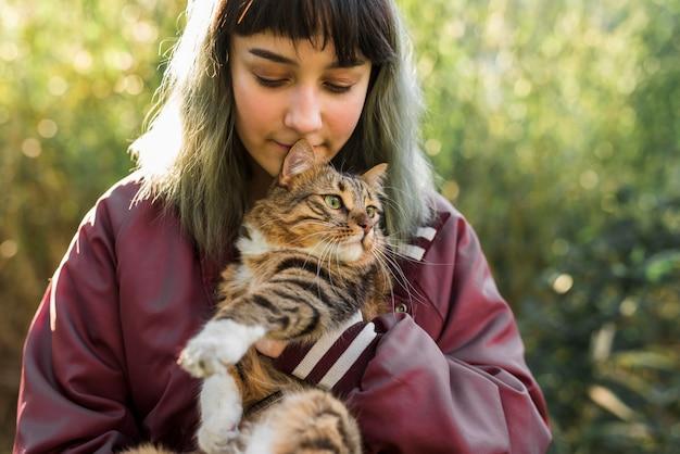 De jonge geverfte haarvrouw koestert haar gestreepte katkat in park Gratis Foto
