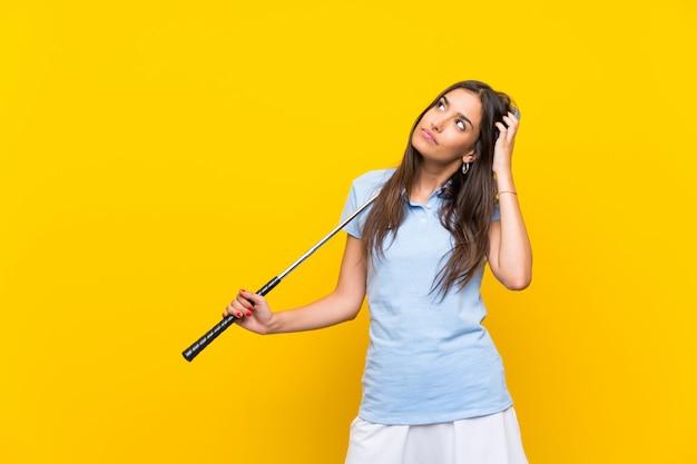 De jonge golfspelervrouw over geïsoleerde gele muur die twijfels hebben en verwart gezichtsuitdrukking Premium Foto
