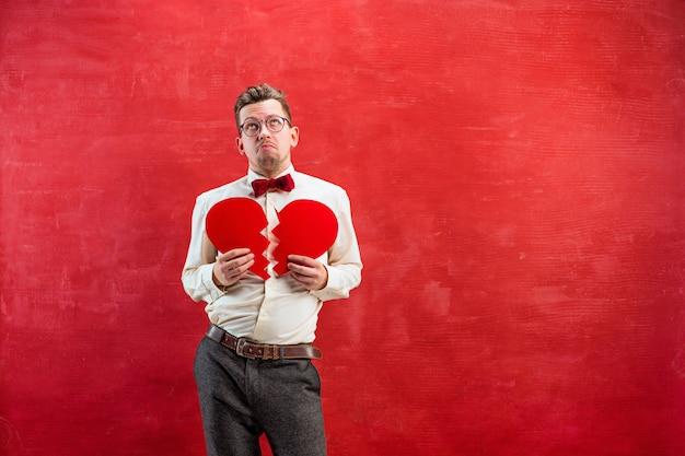 De jonge grappige man met abstracte gebroken hart op rode studio achtergrond. concept - ongelukkige liefde Gratis Foto