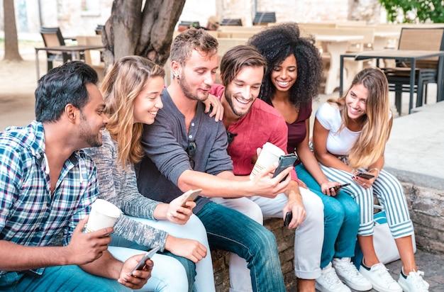 De jonge groep van studentenvrienden gebruikt smartphone met koffie bij universitaire universiteit Premium Foto