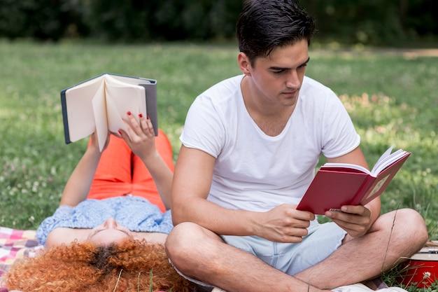 De jonge het houden van boeken van de paarlezing in openlucht Gratis Foto