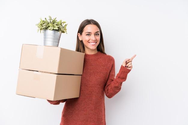 De jonge kaukasische dozen van de vrouwenholding isoleerden opzij glimlachend en richtend, tonend iets op lege ruimte. Premium Foto