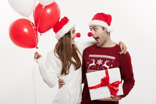 De jonge kaukasische giften van de paarholding, champnage en ballon die grappig gezicht op kerstmis maken. Premium Foto