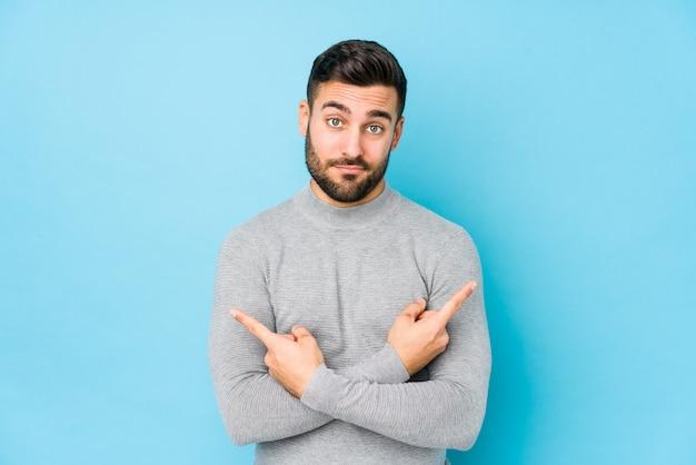 De jonge kaukasische mens tegen een blauwe muur isoleerde zijdelings punten, probeert tussen twee opties te kiezen. Premium Foto