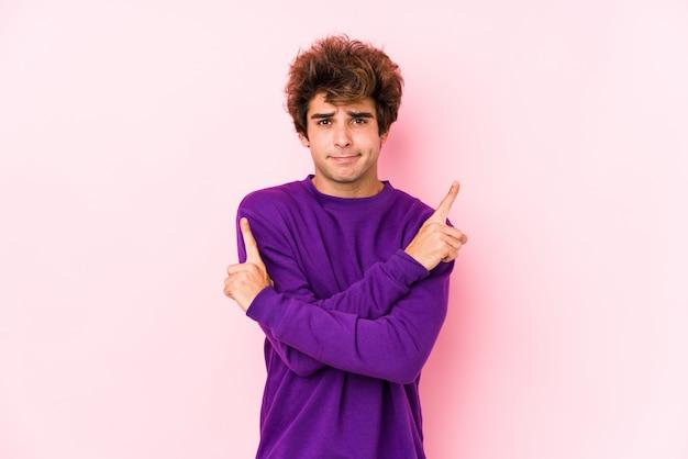 De jonge kaukasische mens tegen een roze muur isoleerde zijdelings punten, probeert tussen twee opties te kiezen. Premium Foto