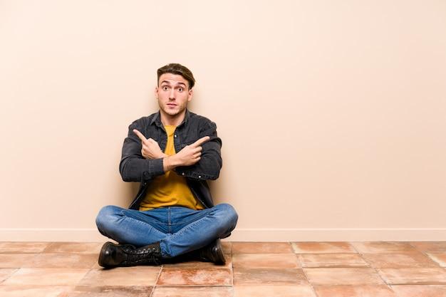 De jonge kaukasische mensenzitting op de vloer isoleerde zijdelings punten, probeert tussen twee opties te kiezen. Premium Foto