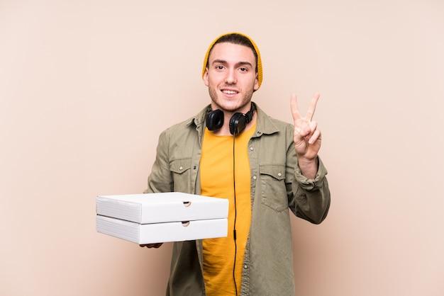De jonge kaukasische pizza's die van de mensenholding nummer twee met vingers tonen. Premium Foto
