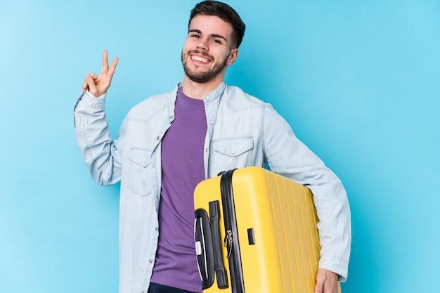 De jonge kaukasische reizigersmens die een koffer houden isoleerde blij en onbezorgd tonend een vredessymbool met vingers. Premium Foto
