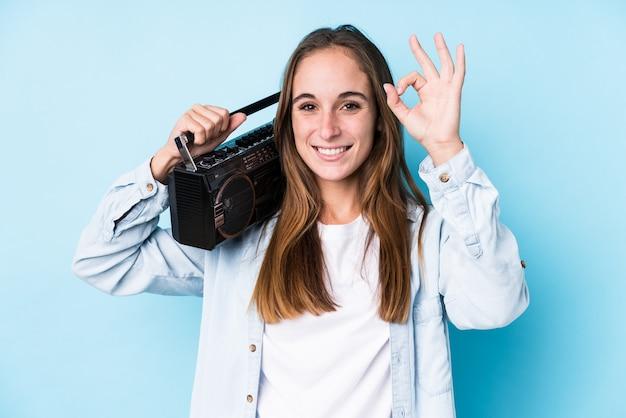 De jonge kaukasische vrouw die een cassete houden isoleerde vrolijk en zeker tonend ok gebaar. Premium Foto