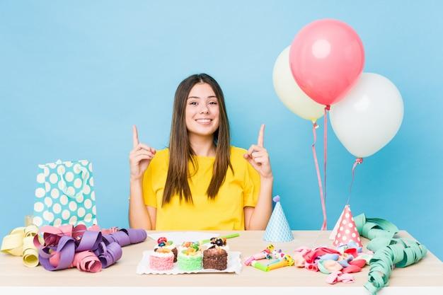 De jonge kaukasische vrouw die een verjaardag organiseert wijst op met beide voorvingers die omhoog een lege ruimte tonen. Premium Foto