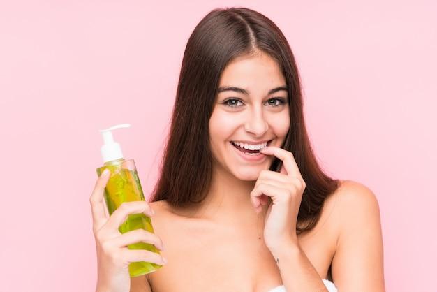 De jonge kaukasische vrouw die een vochtinbrengende crème met aloë vera houden ontspande het denken over iets Premium Foto