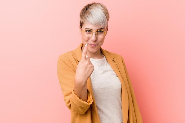 De jonge kaukasische vrouw die toevallige bedrijfskleren dragen die met vinger op u richten alsof uitnodigend komt dichterbij. Premium Foto