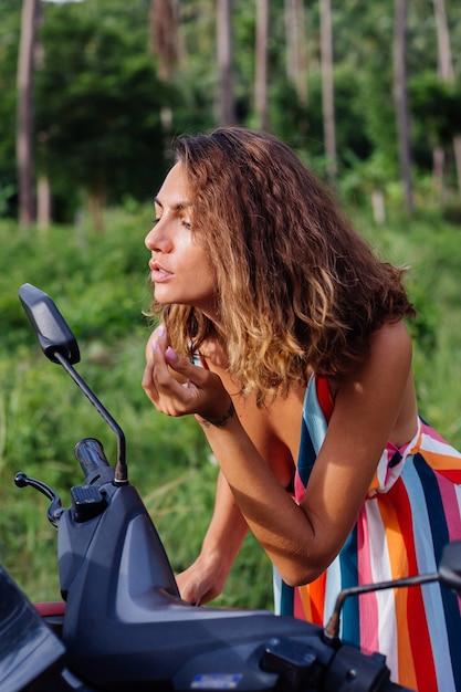 De jonge kaukasische vrouw kijkt in motorfietsspiegel op tropisch gebied Gratis Foto