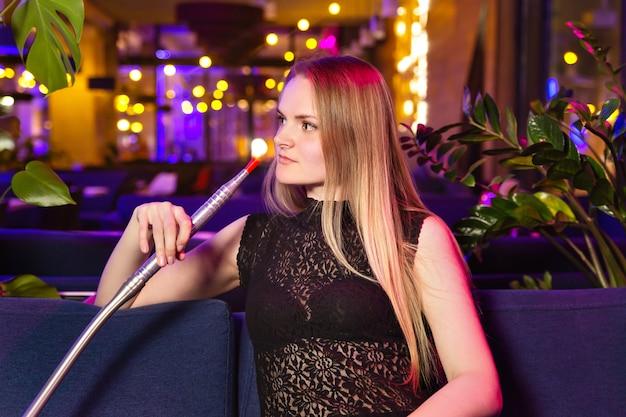 De jonge kaukasische vrouw rookt een waterpijp of shisha in de club of de barrook Premium Foto