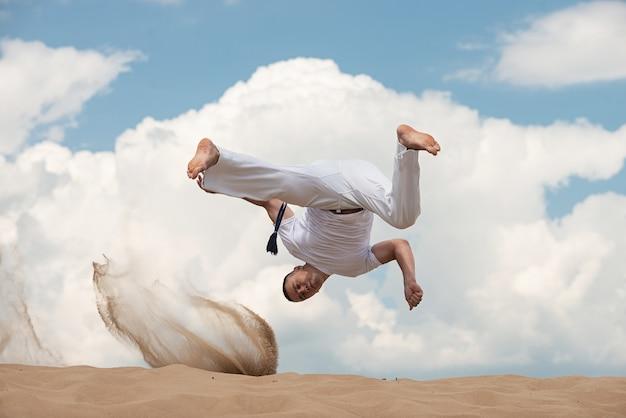 De jonge kerel leidt capoeira op hemel op backround. een man voert martial de trap in de sprong uit Premium Foto