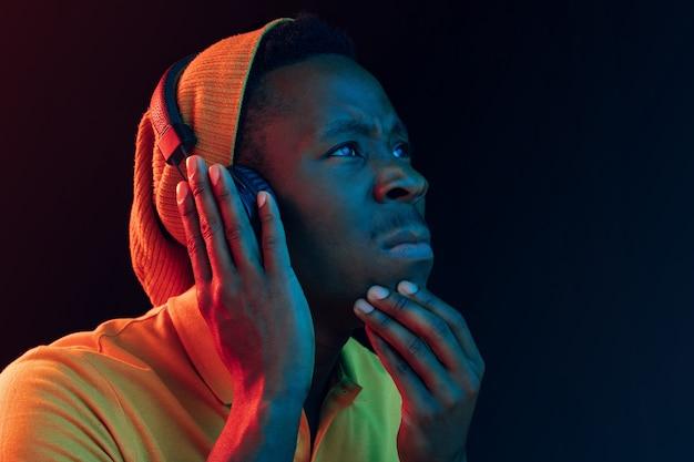 De jonge knappe ernstige triest hipster man luisteren muziek met koptelefoon op zwarte studio met neonlichten. disco, nachtclub, hiphopstijl, positieve emoties, gezichtsuitdrukking, dansconcept Gratis Foto