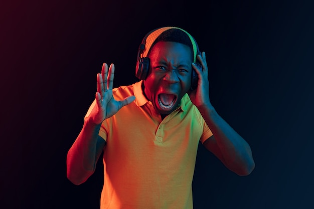 De jonge knappe gelukkig hipster man luisteren muziek met koptelefoon op zwarte studio met neonlichten. disco, nachtclub, hiphopstijl, positieve emoties, gezichtsuitdrukking, dansconcept Gratis Foto