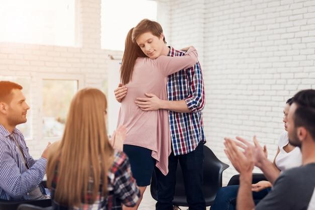 De jonge knappe man omhelst meisje op vergadering. Premium Foto