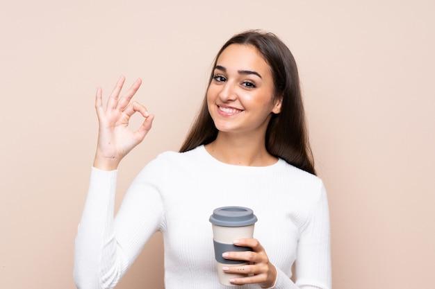De jonge koffie van de vrouwenholding om weg te nemen terwijl het maken van ok teken Premium Foto