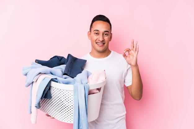 De jonge latijnse mens die vuile kleren opnemen isoleerde vrolijk en zeker tonend ok gebaar. Premium Foto