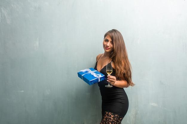 De jonge latijnse vrouw die een gift en een champagnekop houdt, heeft zij pret. Premium Foto