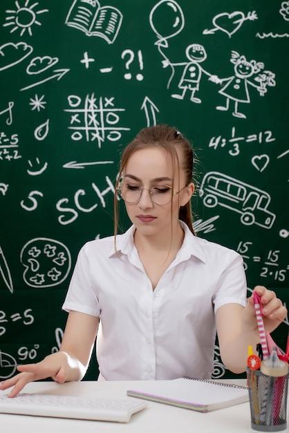 De jonge leraar zit dichtbij bord in klaslokaal Premium Foto