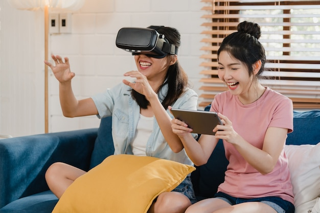 De jonge lesbische lgbtq aziatische vrouwen koppelen thuis het gebruiken van tablet Gratis Foto