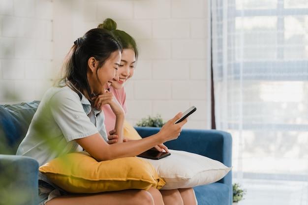 De jonge lesbische lgbtq-vrouwen koppelen thuis het gebruiken van mobiele telefoon Gratis Foto