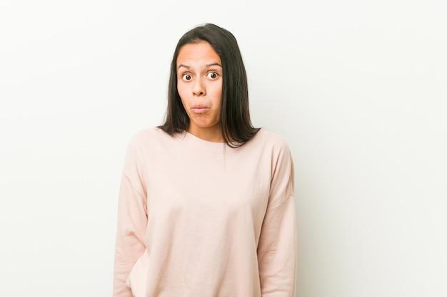De jonge leuke spaanse tienervrouw haalt schouders op en verwarde open ogen. Premium Foto