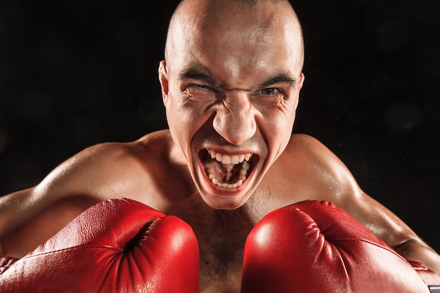 De jonge man kickboksen op zwart met schreeuwend gezicht Gratis Foto