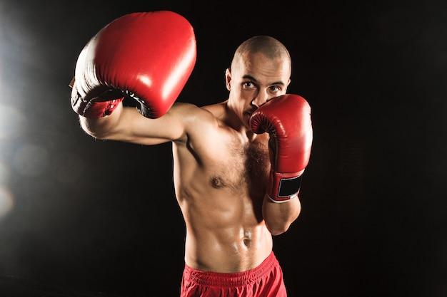 De jonge man kickboksen op zwart Gratis Foto