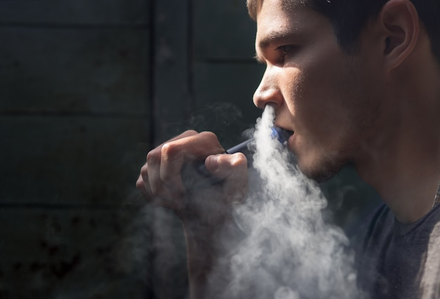 De jonge man met de elektronische sigaret Premium Foto