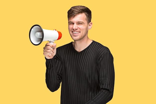 De jonge man met een megafoon op gele achtergrond Gratis Foto