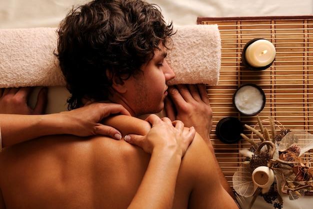 De jonge man op kuur - recreatie, rust, ontspanning en massage. hygh kijkhoek Gratis Foto