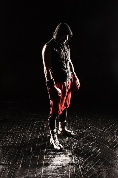 De jonge mannelijke atleet kickboksen die zich tegen zwarte achtergrond bevindt Gratis Foto