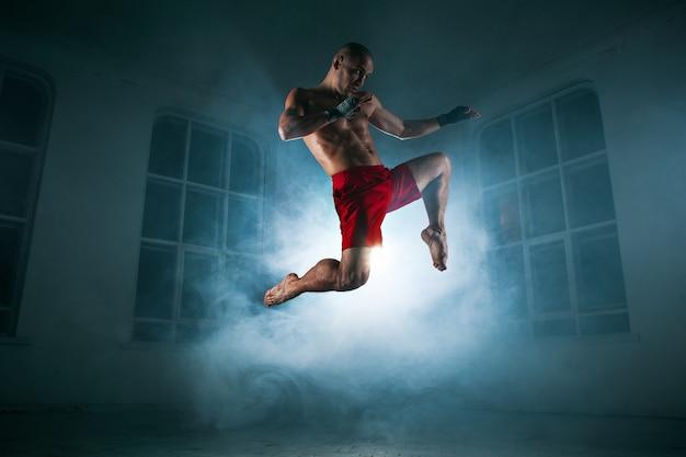 De jonge mannelijke atleet kickboksen op een blauwe rook Gratis Foto
